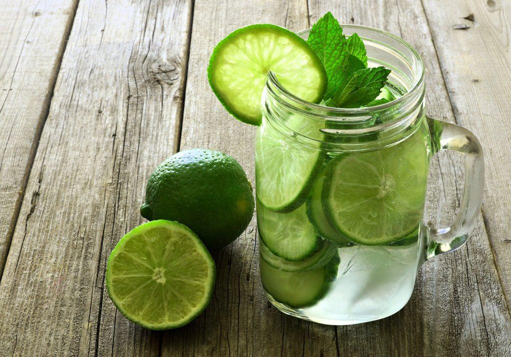 Limões e água com limão no copo de vidro