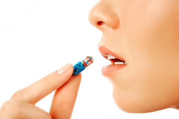 Mulher colocando comprimido do remédio Tesofensina na boca