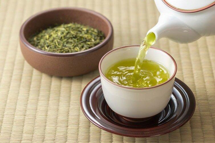 Folhas do chá verde e o chá em uma xícara