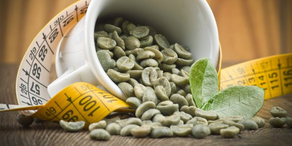 Café verde em grãos e fita métrica