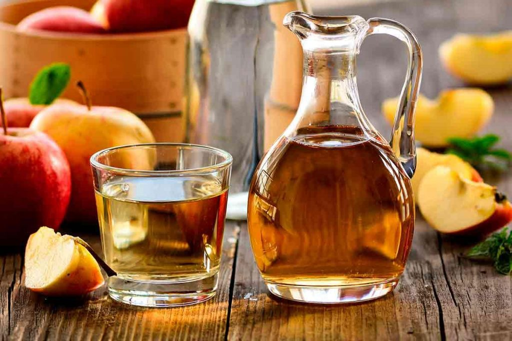 Jarra e copo de vidro com chá feito de vinagre de maça