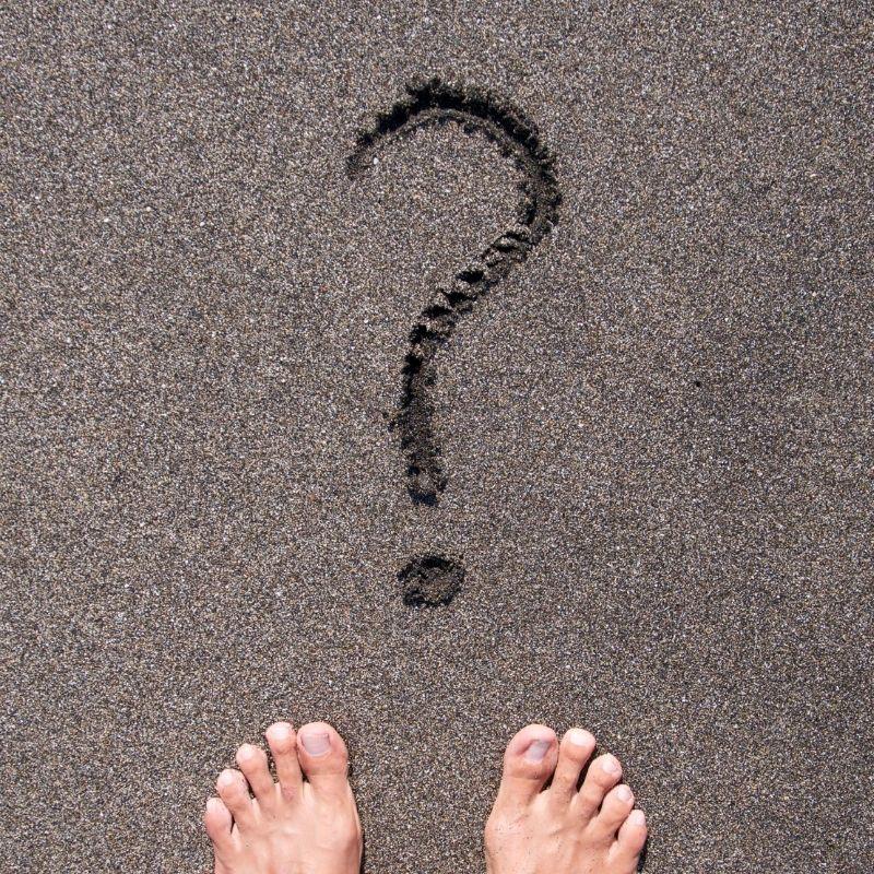 Ponto de interrogação escrito na areia e um pé de uma pessoa.