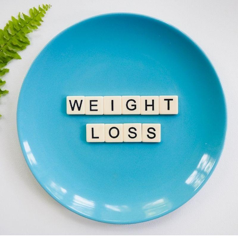 Weight loss escrito com bloquinhos de letras em um prato azul.
