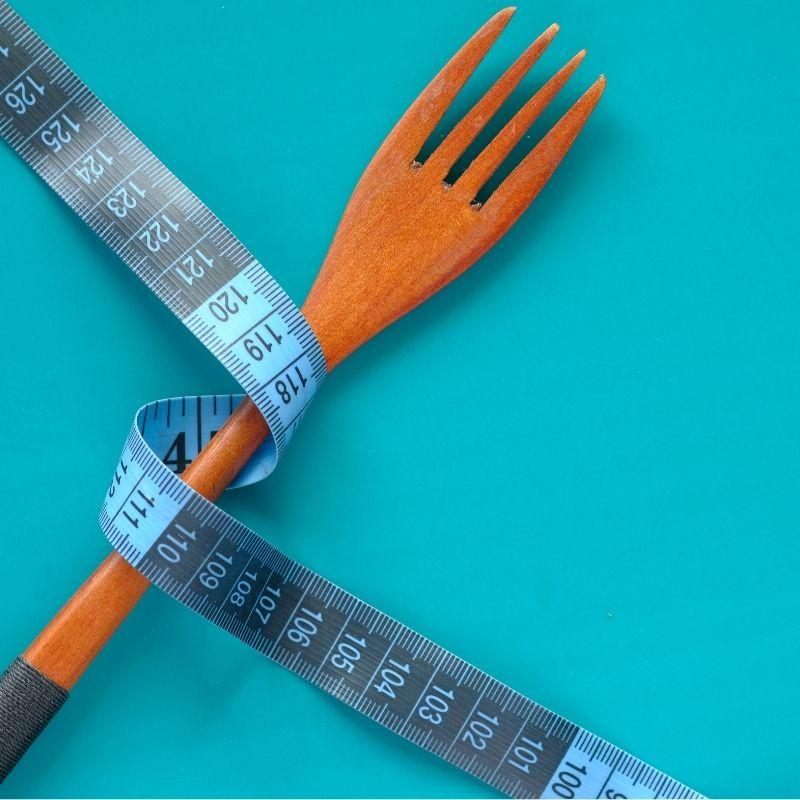Um garfo de madeira e uma fita métrica azul.