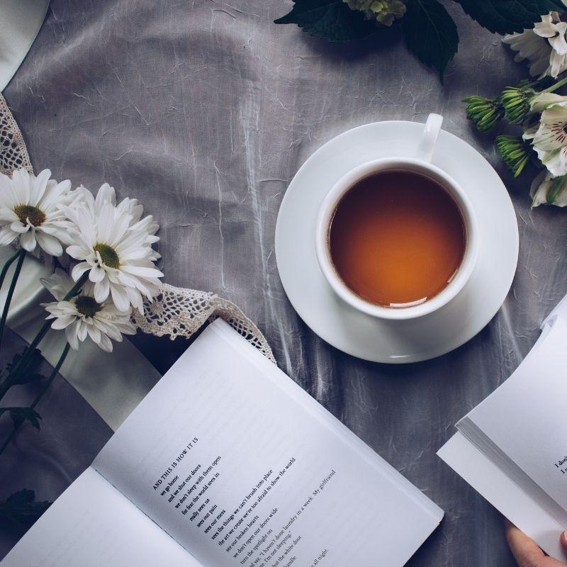 Xícara de chá sobre uma mesa enfeitada com flores e livros.