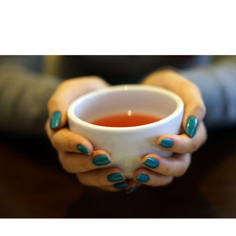mulher segurando uma xícara de chá com as duas mãos.