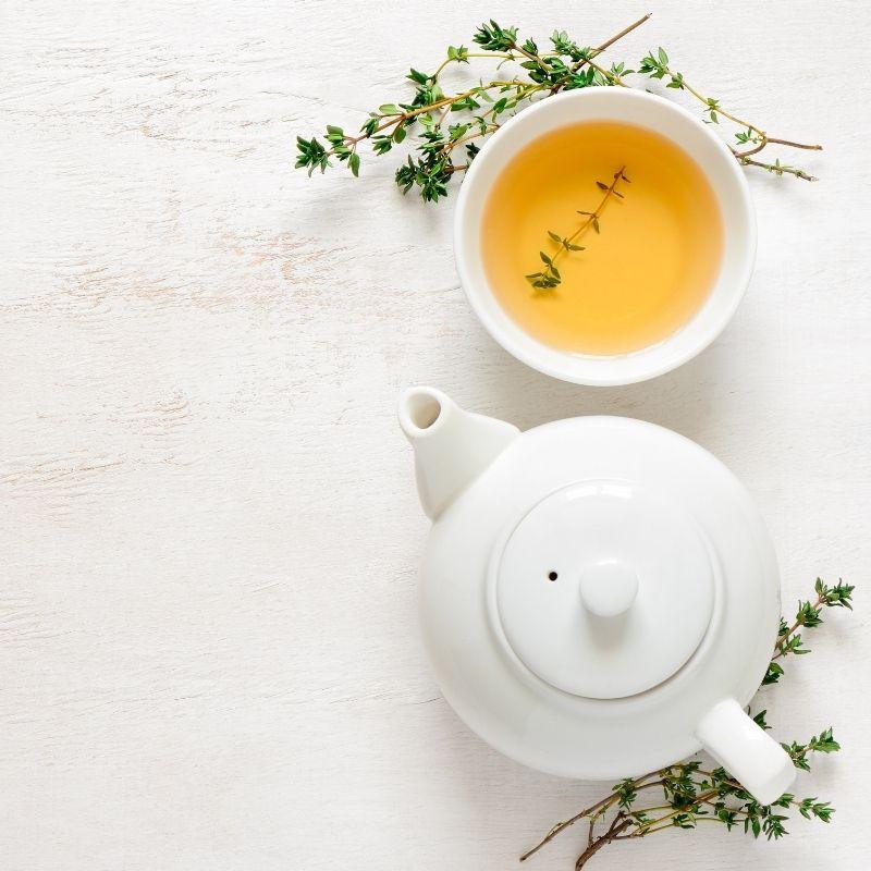 Xicara de chá ao lado de um bule ambos de porcelana branca.