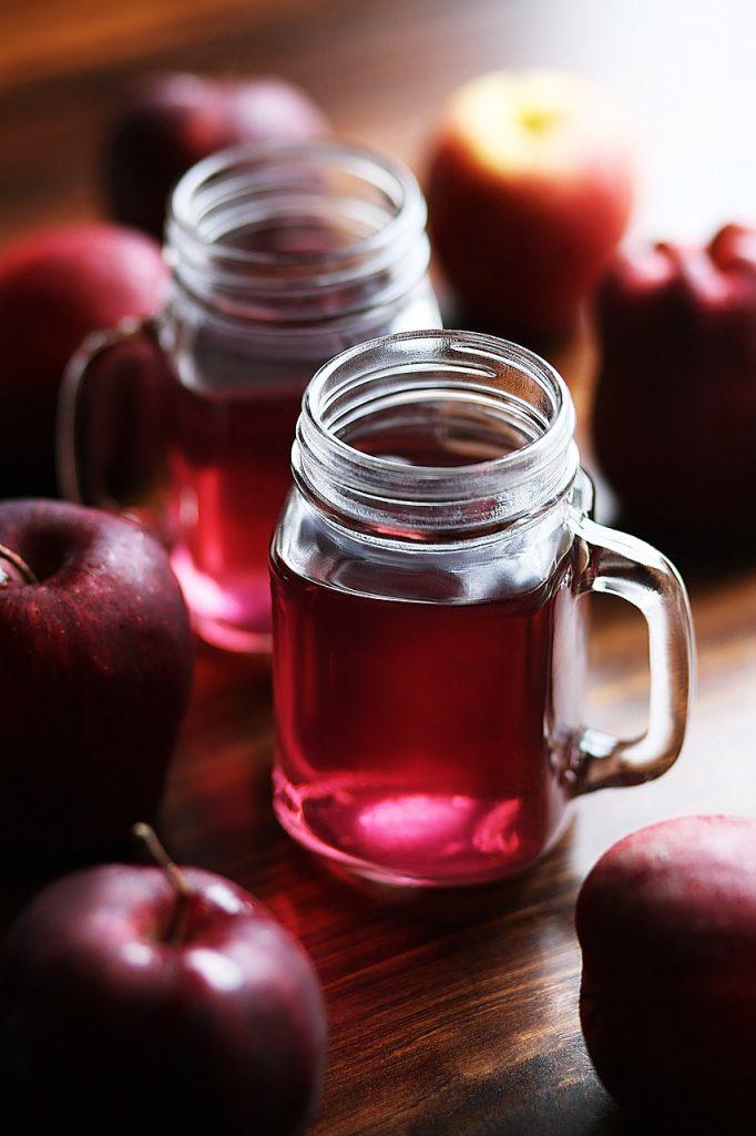 Suco cranberry em uma caneca transparente, sobre uma mesa de madeira com frutas cranberry ao lado.