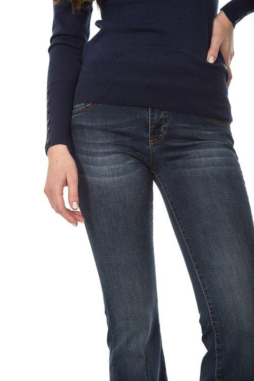 Mulher magra vestindo calça jeans e suéter azul marinho, com a mão na cintura.