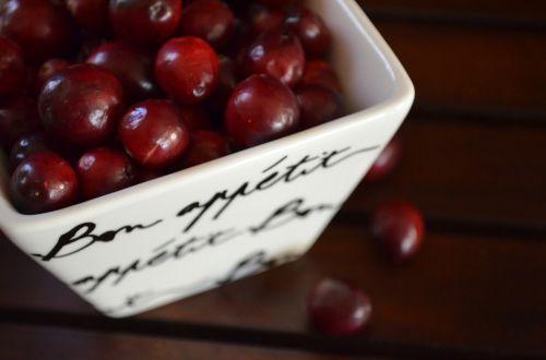 Fruta Cranberry em um copo quadrado de porcelana, sobre uma mesa de madeira escura.