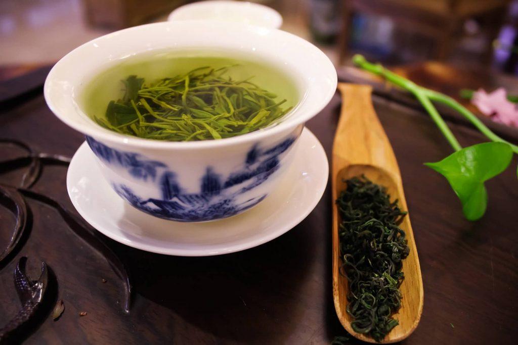 Chá de erva doce em uma xicara branca com uma colher de pau ao lado contendo ervas, sobre uma mesa de madeira escura.