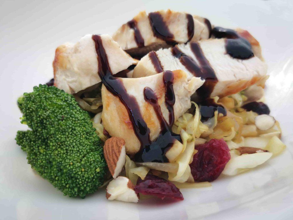 Foto de um prato com alimentos saudáveis, frango, brócolis, nozes, passas, entre outros.