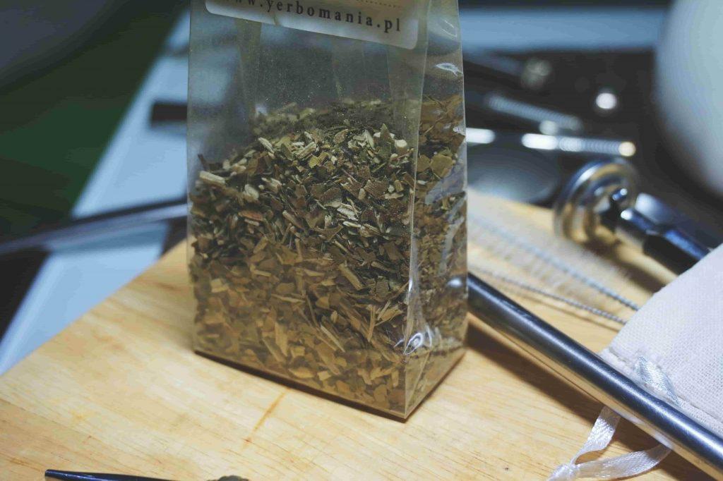 Saco com a erva mate seca, em uma mesa com objetos de preparação.