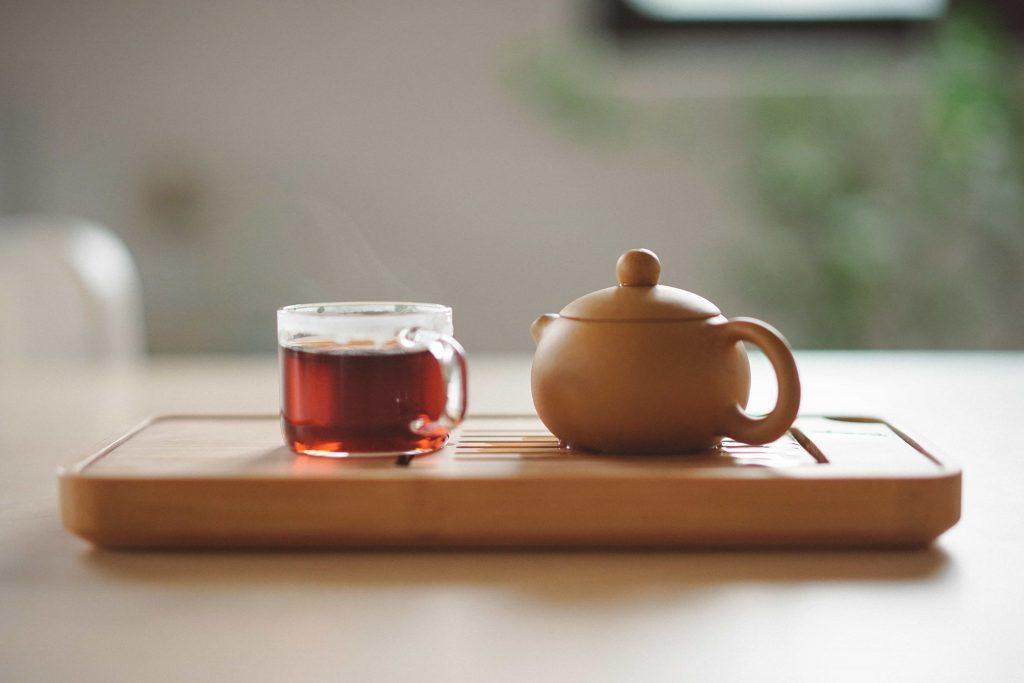 Delicada Xícara de chá contendo mate ao lado um pequeno bule de chá de barro, sobre uma suporte de madeira.