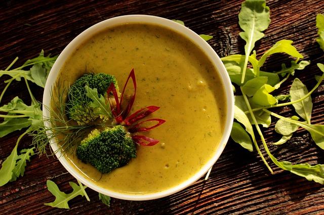 imagem de uma sopa de verduras e legumes sobre uma mesa enfeitada com rúculas.