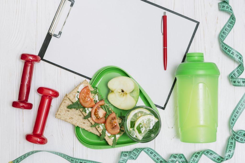 prancheta de anotações, caneta, lanche de sanduiche com maçã, uma garrafinha verde e um alteres vermelho sobe uma superfície branca.