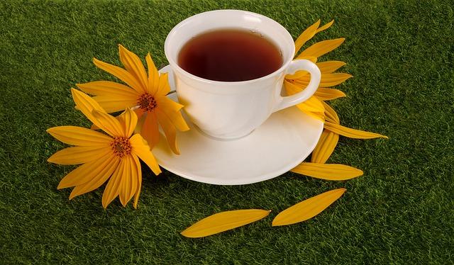 imagem de uma xicara com chá,  sobre uma superfície com grama e flores amarelas.