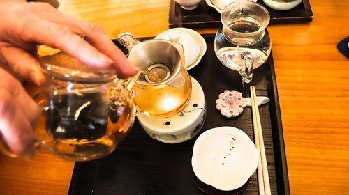 Pessoa servindo chá em uma mesa.