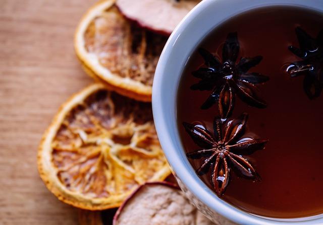 Chá de Anis Estrelado em uma xicara branca sobre uma mesa de madeira enfeitada com frutas secas.
