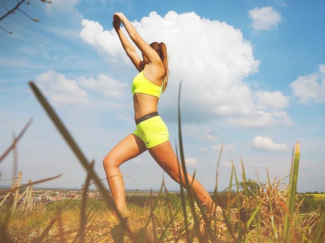 Mulher magra fazendo alongamento em um campo.